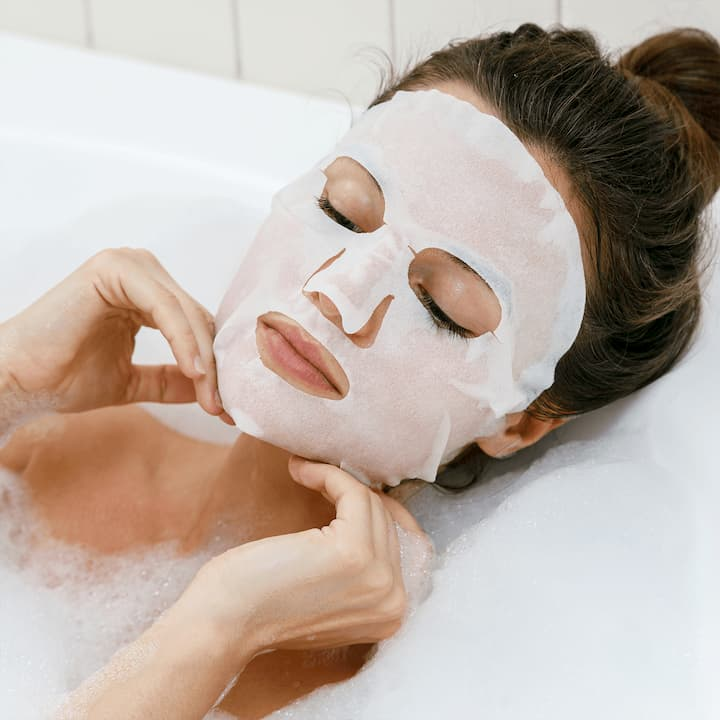 girl having a bath and a sheet mask on her face