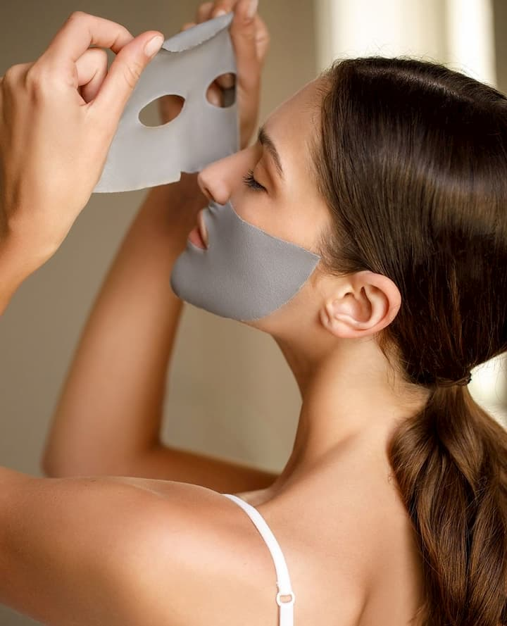 girl removing face sheet mask from her face