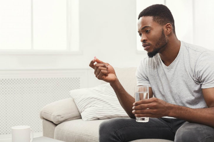 man-holding-glass-of-water-and-pill-of-anticids-taking-medication