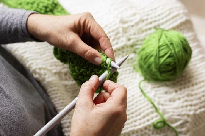 high-view-person-knitting-with-green-thread