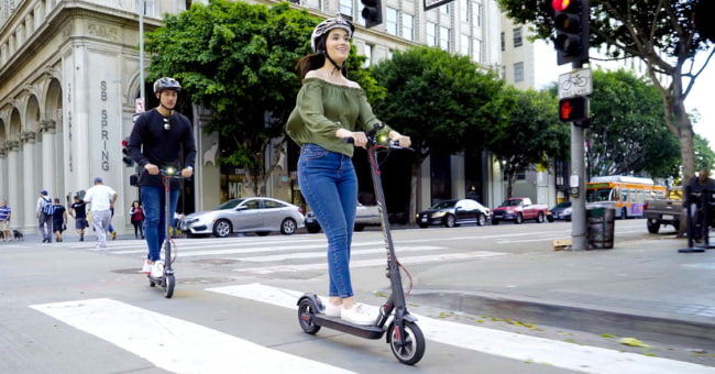 girl and boy riding electric scooters