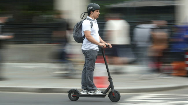 young man commuting with an electric scooter