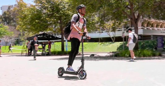 young man riding an electric scooter in australia