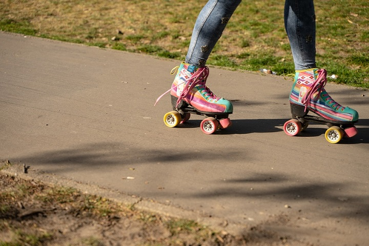 picture of a little girl in jeans and stylish roller skates in a park